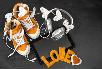 Love for music concept.Orange sneakers, headphones, tablet and h