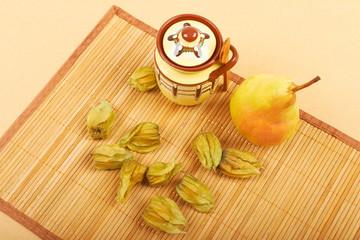 Physalis fruits, pear and ceramic sugar bowl on a bamboo napkin