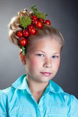 Portrait of cute girl with wreath of tomatoes