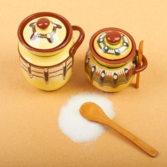 Sugar bowls  with a wooden spoon and lid on a beige background