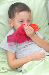 Boy is lying in bed and blows her nose