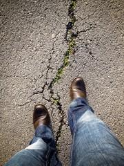 man walking through a crack