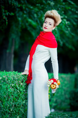 Bride in a white dress and a long red scarf on the nature
