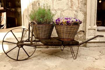 old wheelbarrow with baskets of flowers