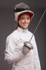 girl in white fencing costume. with sword and  fencing mask