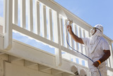 House Painter Spray Painting A Deck of A Home - 75720252