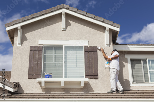 House Painter Painting the Trim And Shutters of Home - 75720233