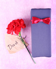 Happy Father's Day with gift box, red carnation and piece of