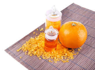Bottles of essential oil and bath salt near orange