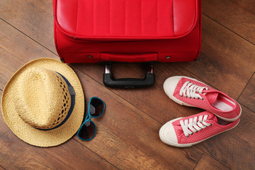 Suitcase and tourist stuff on floor close-up