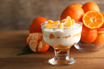Tasty milk dessert with fresh tangerine pieces in glass bowl,