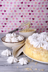 Tasty homemade meringue cake on wooden table, on pink