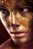 Girl with gold paint on face with face art and body art