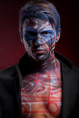 A creepy portrait of a man with bloody body art and face art