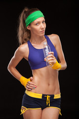 portrait of a healthy young woman drinking bottle of water