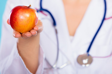Nutritionist holding apple fruit in her hand