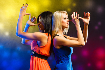 Women in evening dresses dancing in the club