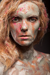 Portrait of young woman covered in healing clay. Face art.