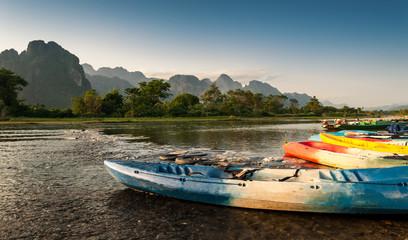 kayak and longtail boats in Nam Song river at Vang Vieng, Laos