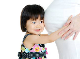 Asian child listening to pregnant mother's stomach
