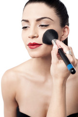 Pretty woman applying makeup with brush