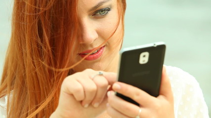 Red haired woman using smartphone on beach