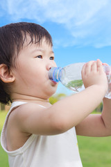 Little asian girl  drinking water from plastic bottle