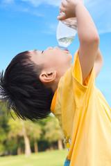 Little asian boy drinking water from plastic bottle