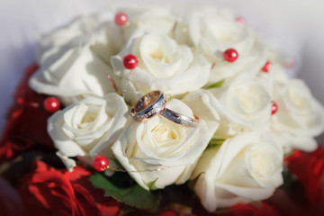 Gold wedding rings on a bouquet of beige roses
