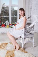 Pregnant women sit on a chair relaxing near window