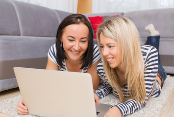 Two young women using computer in living room