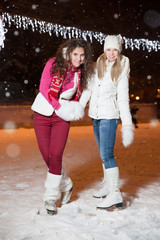 two beautiful girls ice skating outdoor on a warm winter night