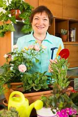 elderly woman working with fresh flowers in pots