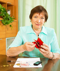 Senior woman with purse in home