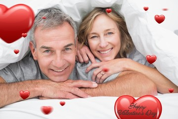 Composite image of loving couple under the duvet