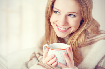 happy woman is under blanket and  cup of coffee