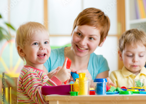 Leinwanddruck Bild woman playing and teaching with children