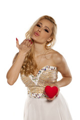 young woman in elegant dress holding heart and sends a kiss