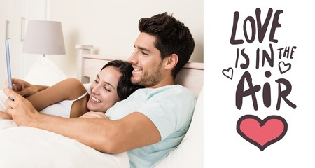 Composite image of attractive couple lying in bed with tablet pc