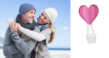 Couple hugging on the beach in warm clothing