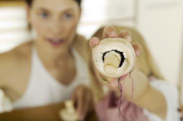 Kleines Mädchen (4-5) hält Pilz,Pilze, Mutter im Hintergrund