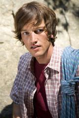 Junger Mann mit dem Kletterseil auf den Schultern, close-up