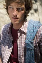 Junger Mann in den Bergen trägt Kletterseil