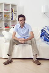Junger Mann sitzt auf dem Sofa im Wohnzimmer, Portrait