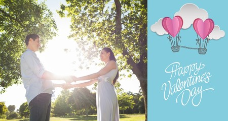 Composite image of loving young couple holding hands at park