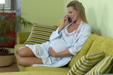 Schwangere Frau, die auf Sofa mit Telefon