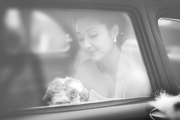 Portrait of the bride in a window of a wedding retro of the car