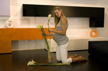 Schwangere Frau Anordnen von Blumen in Glasvase