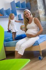 Schwangere Mutter hält Becher, Tochter (3-4) stand auf
