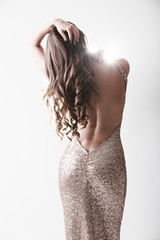 Beautiful woman in elegant evening shiny dress with naked rear